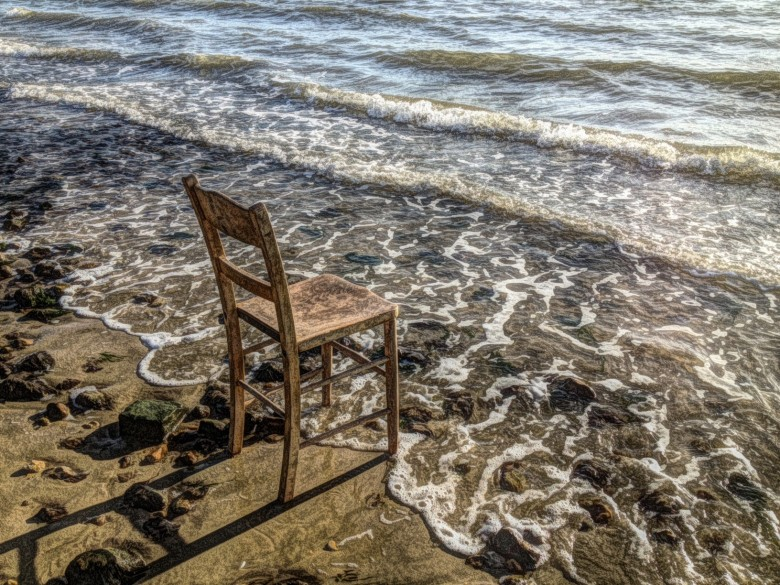 Wooden chair resting on a shoreline